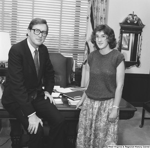 "[""Senator John D. (Jay) Rockefeller sits on the edge of the desk in his Dirksen office and poses for a photograph with an unidentified individual.""]%"