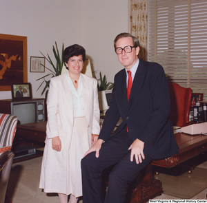 "[""In this color photo, Senator John D. (Jay) Rockefeller sits on the edge of his desk with an unidentified woman.""]%"