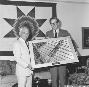 "[""Senator John D. (Jay) Rockefeller holds a framded photograph of a coal barge crossing under a bridge, an apparent gift from the unidentified man on his right.""]%"