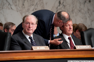 "[""Senator Max Baucus is briefed by an adviser during a Finance Committee hearing about health care reform.""]%"