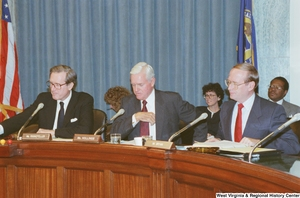 "[""Senator John D. (Jay) Rockefeller sits with two other Senators at a Commerce Committee hearing.""]%"