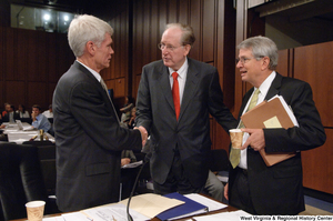 "[""Senator John D. (Jay) Rockefeller shakes hands with two unidentified men at an executive session of the Finance Committee.""]%"