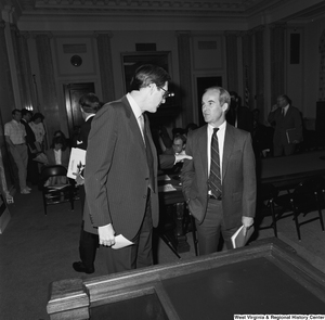 "[""Senator John D. (Jay) Rockefeller stands next to an unidentified man in a Senate building.""]%"