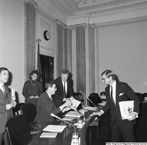 "[""Senator John D. (Jay) Rockefeller takes papers from an adviser before a Senate committee hearing.""]%"