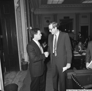 "[""Senator John D. (Jay) Rockefeller shakes hands with an unidentified man in a Senate hearing room.""]%"