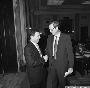 "[""Senator John D. (Jay) Rockefeller shakes hands and laughs with an unidentified man in a Senate hearing room.""]%"