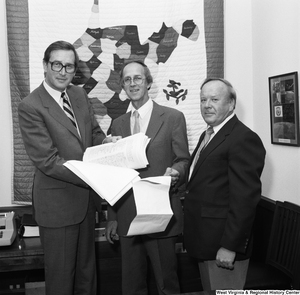 "[""Senator John D. (Jay) Rockefeller holds a stack of papers and poses for a photograph with the County Commissioner from Marshall County, West Virginia.""]%"