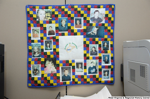 "[""A quilt that reads \""Promise to Remember 2003\"" hangs on a wall in Senator John D. (Jay) Rockefeller's office.""]%"