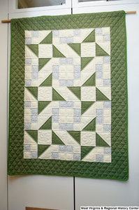 "[""A green, blue, and white geometric quilt hangs in Senator John D. (Jay) Rockefeller's office.""]%"