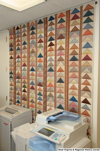 "[""A colorful geometric quilt hangs behind a photocopier on a wall in Senator John D. (Jay) Rockefeller's office.""]%"