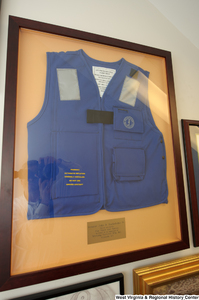 "[""A life vest hangs on a wall in Senator John D. (Jay) Rockefeller's office. The plaque reads: \""Senator John D. Rockefeller IV, For all you do for our State and Nation on behalf of the employees of Mustang Survival Mfg. Inc. Ellizabeth, WV\"".""]%"