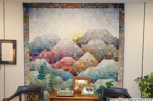 "[""A colorful quilt hangs behind two chairs and a table in Senator John D. (Jay) Rockefeller's office.""]%"
