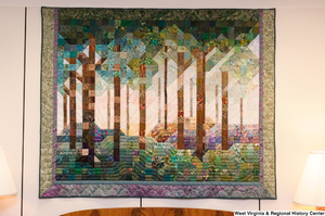 "[""This photo shows a colorful forest quilt hanging in Senator John D. (Jay) Rockefeller's office.""]%"