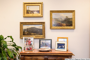 "[""Three paintings hang in Senator Rockefeller's office above a table with photographs of some of his family members.""]%"