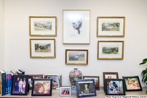 "[""Many photographs and paintings hang on a wall and sit on a table in Senator John D. (Jay) Rockefeller's office.""]%"