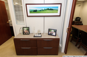 "[""Crystal figures and Rockefeller family photos sit on some drawers in the Senator's office.""]%"