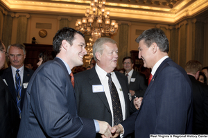 "[""Senator Joe Manchin shakes hands with an unidentified man at an event in the Senate.""]%"