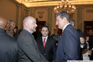 "[""Senator Joe Manchin shakes hands with an unidentified man during his swearing-in ceremony.""]%"