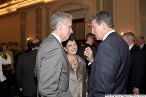"[""Senator Joe Manchin speaks with two unidentified individuals during his swearing-in ceremony.""]%"