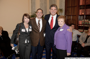 "[""Senator Joe Manchin poses for a photograph with three individuals after his swearing-in ceremony.""]%"