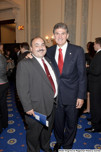 "[""Senator Joe Manchin stands with an unidentified man after his swearing-in ceremony.""]%"