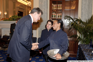"[""Senator Joe Manchin shakes hands with a US Capitol Building staff member after his swearing-in ceremony.""]%"