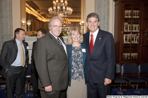 "[""Senator Joe Manchin stands with two supporters after his Senate Swearing-In Ceremony.""]%"