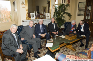 "[""A group of six Senators sit together during a small event.""]%"