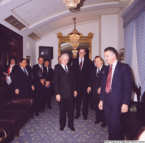 "[""This color photograph shows several senators including Senators Robert C. Byrd and John D. (Jay) Rockefeller and former Senator Jennings Randolph stand together in a room outside the Senate to celebrate Senator Byrd's birthday.""]%"
