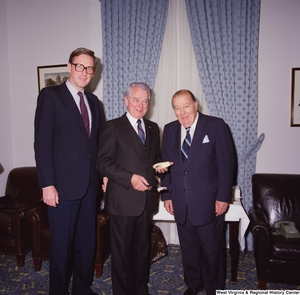 "[""Senator Robert C. Byrd holds a piece of cake during his birthday celebration and stands for a photograph beside Senator John D. (Jay) Rockefeller and former Senator Jennings Randolph.""]%"