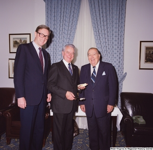 "[""Senator Robert C. Byrd holds a piece of cake during his birthday celebration and stands for a photograph with Senator John D. (Jay) Rockefeller and former Senator Jennings Randolph.""]%"