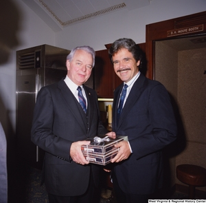 "[""During his birthday celebration, Senator Robert C. Byrd receives a gift from a Senate colleague.""]%"