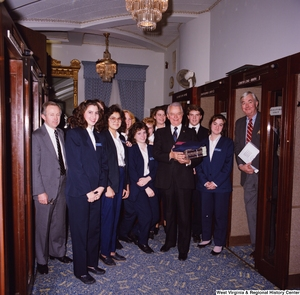 "[""Senator Robert C. Byrd stands for a photograph with a group of Senate pages during his birthday celebration.""]%"