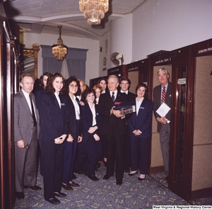 "[""Senator Robert C. Byrd stands for a photograph with a group of Senate pages after his birthday celebration.""]%"