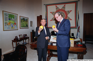 "[""Senator John D. (Jay) Rockefeller inspects Florida oranges in his office with Senator Bob Graham.""]%"