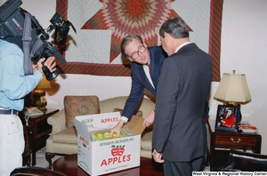 "[""Senator John D. (Jay) Rockefeller shows Florida Senator Bob Graham a box of West Virginia apples.""]%"