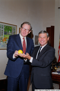 "[""Senator John D. (Jay) Rockefeller and Senator Bob Graham pose for a photograph with a Florida orange.""]%"