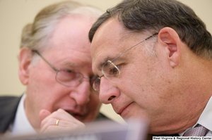 "[""Senator John D. (Jay) Rockefeller whispers to Senator John Boozman during a Commerce Committee hearing.""]%"