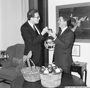 "[""Senator John D. (Jay) Rockefeller stands next to Senator John Breaux who is holding an apple and a football helmet.""]%"