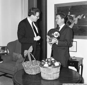 "[""Senator John D. (Jay) Rockefeller stands next to Senator Breaux who is holding a football helmet. The two had a friendly bet against who would win the upcoming Marshall/NLU football game.""]%"