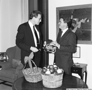 "[""Senator John D. (Jay) Rockefeller speaks to Senator John Breaux who holds a football helmet.""]%"