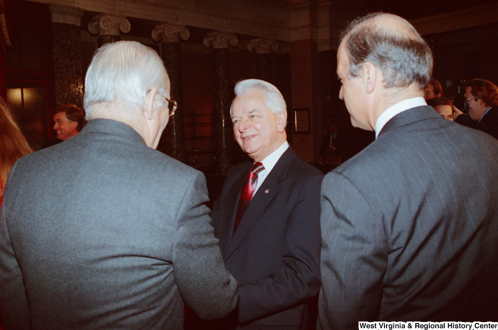 "[""Senator Robert C. Byrd speaks with two unidentified men after Senator John D. (Jay) Rockefeller's second Senate Swearing-In Ceremony.""]%"