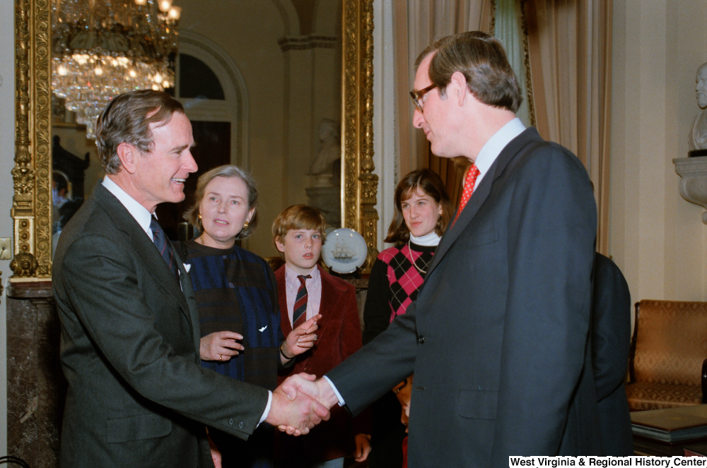 "[""Senator John D. (Jay) Rockefeller shakes hands with Vice President George H. W. Bush following the Senate Swearing-In Ceremony.""]%"
