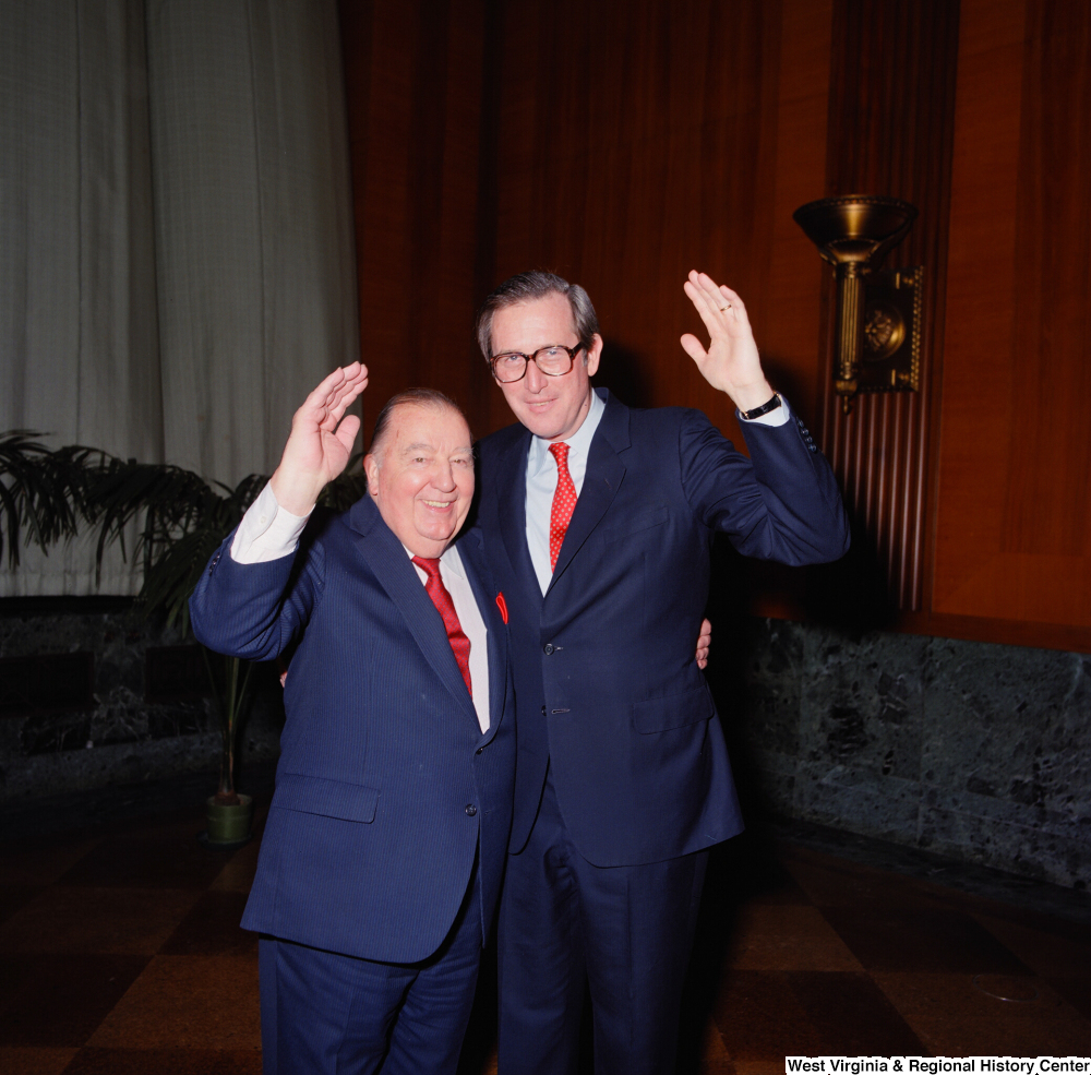 "[""Senator John D. (Jay) Rockefeller and former senator Jennings Randolph raise a hand for a photo following the Senate Swearing-In Ceremony.""]%"