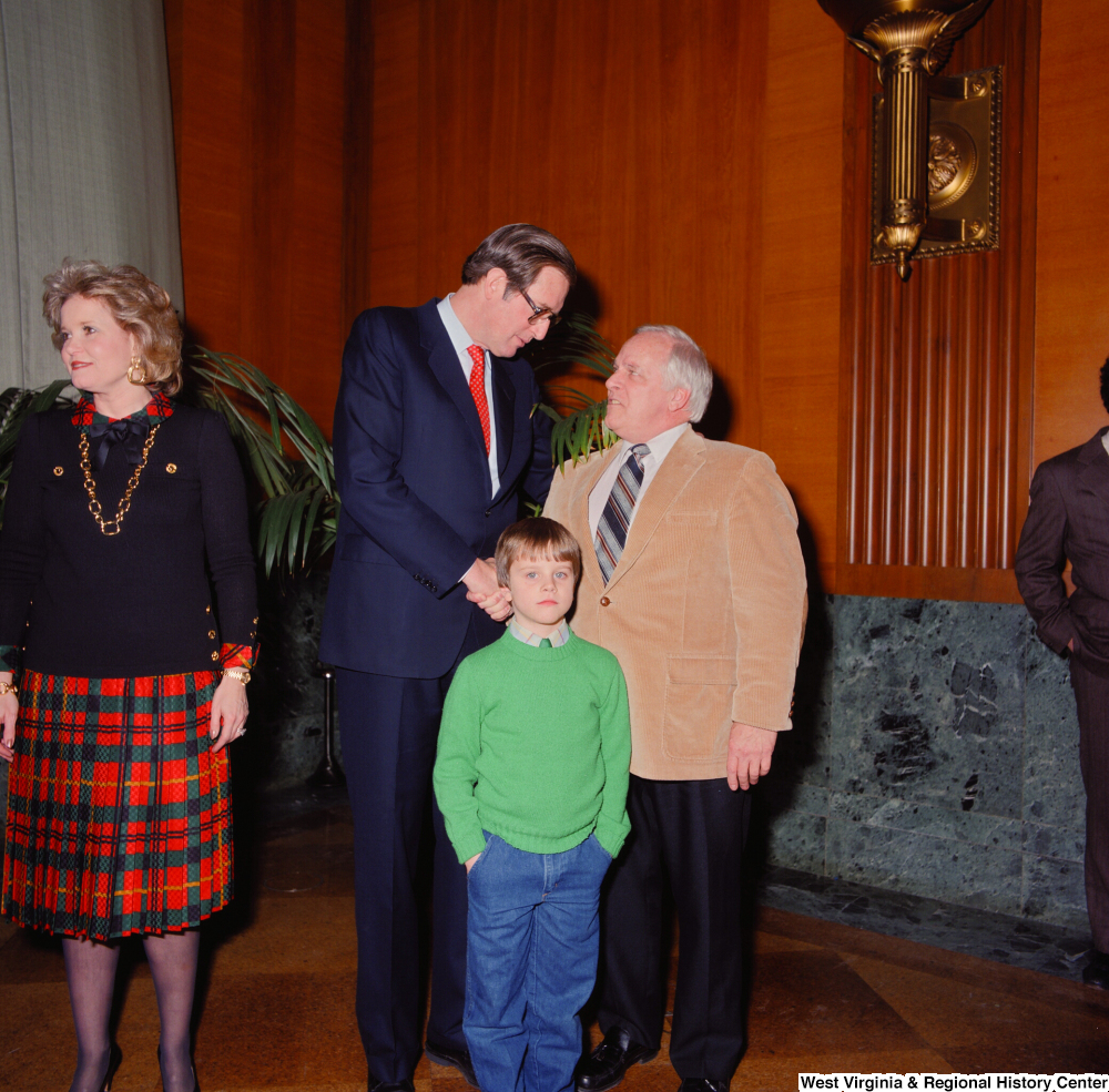 "[""A young child wearing green looks into the camera as Senator John D. (Jay) Rockefeller shakes hands with the unidentified man behind him.""]%"