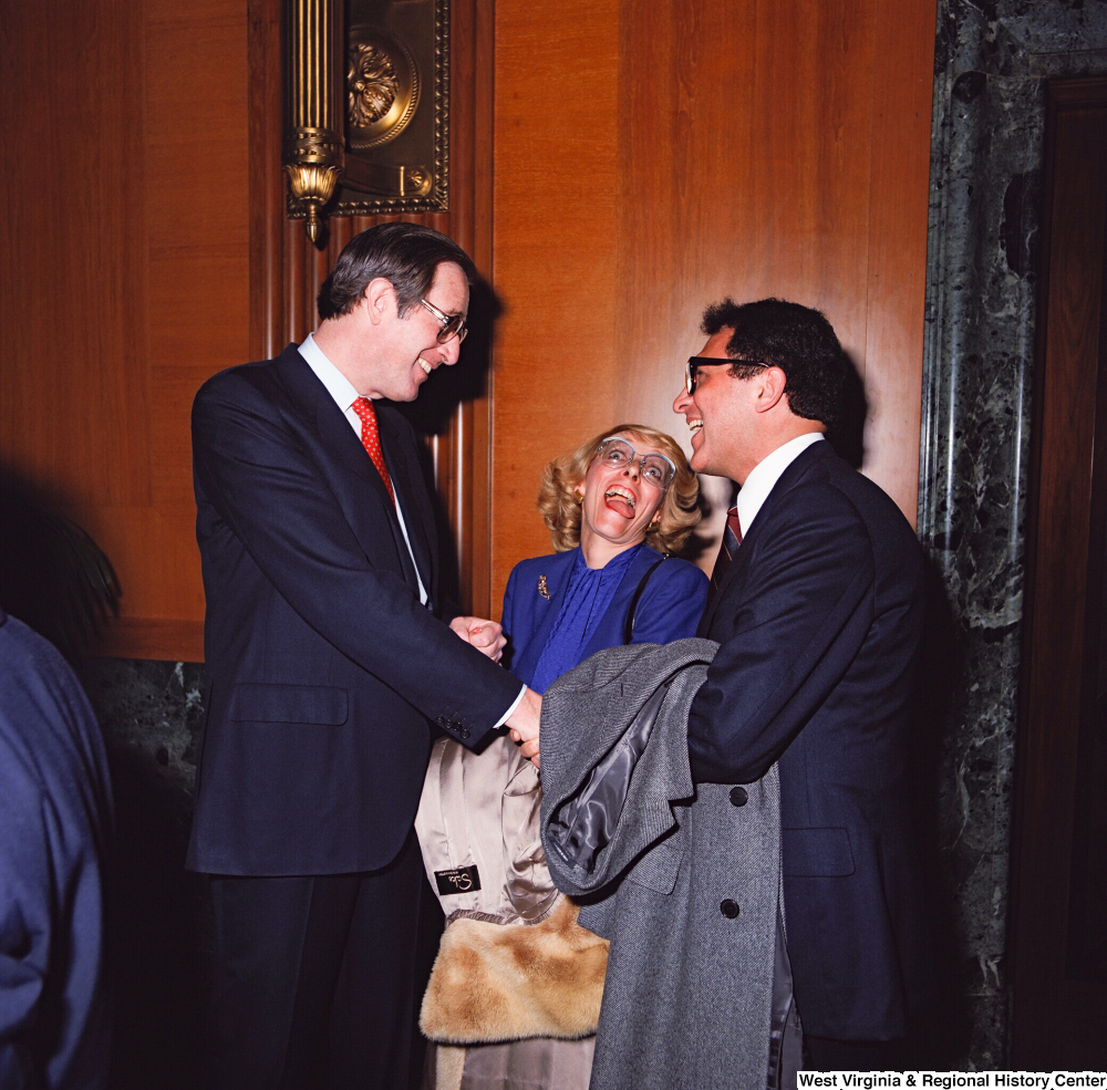 "[""Senator John D. (Jay) Rockefeller shakes hands and laughs with an unidentified supporter as an unidentified woman in the background makes a funny face.""]%"