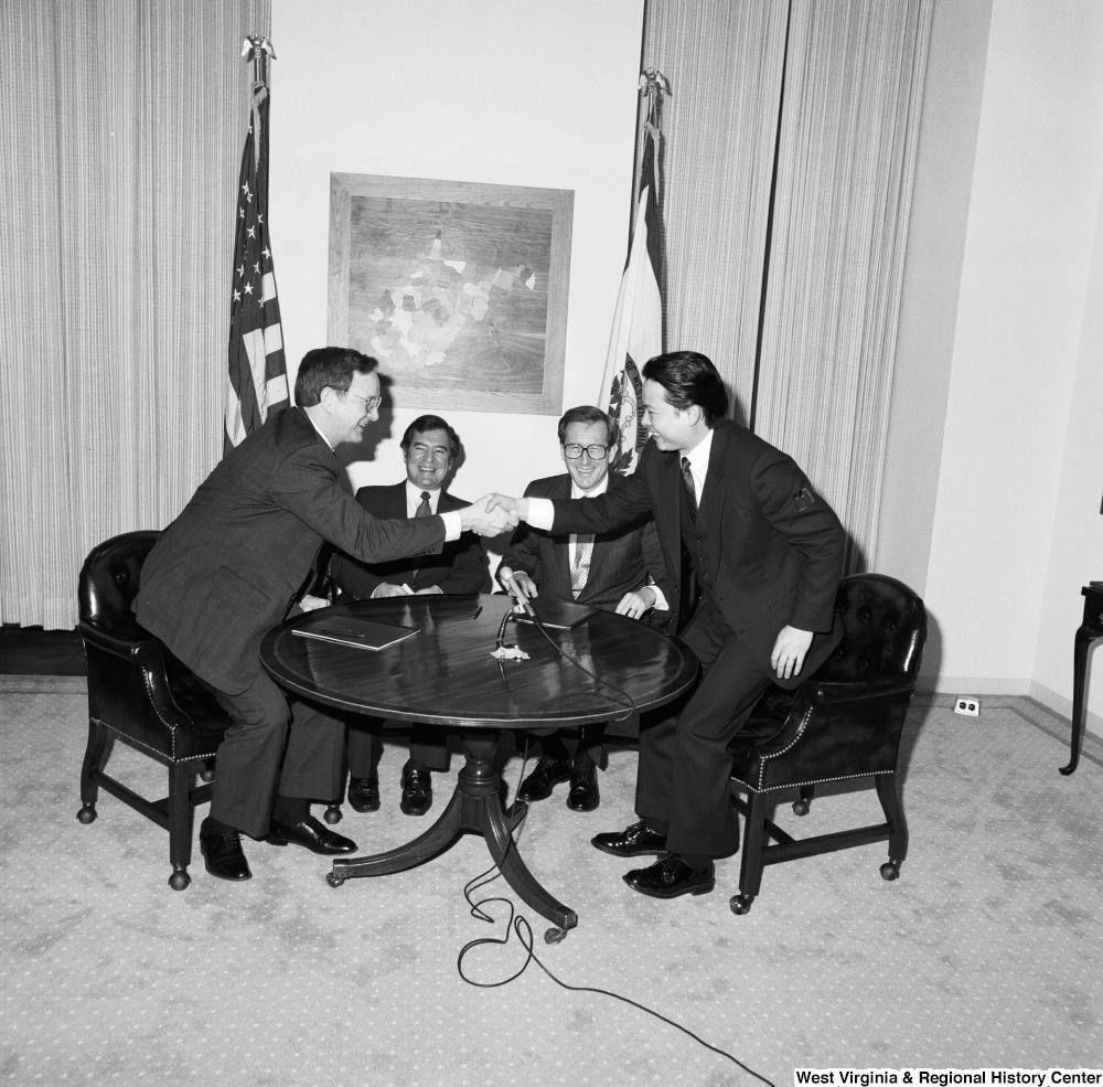 "[""Senator John D. (Jay) Rockefeller and Congressman Nick Rahall sit at a table as representatives from China Steel and the Island Creek Coal Company shake hands after an agreeing on a new contract.""]%"
