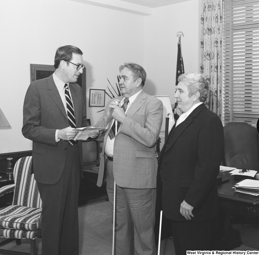"[""Senator John D. (Jay) Rockefeller speaks with two individuals from the West Virginia Chapter of the National Federation of the Blind.""]%"