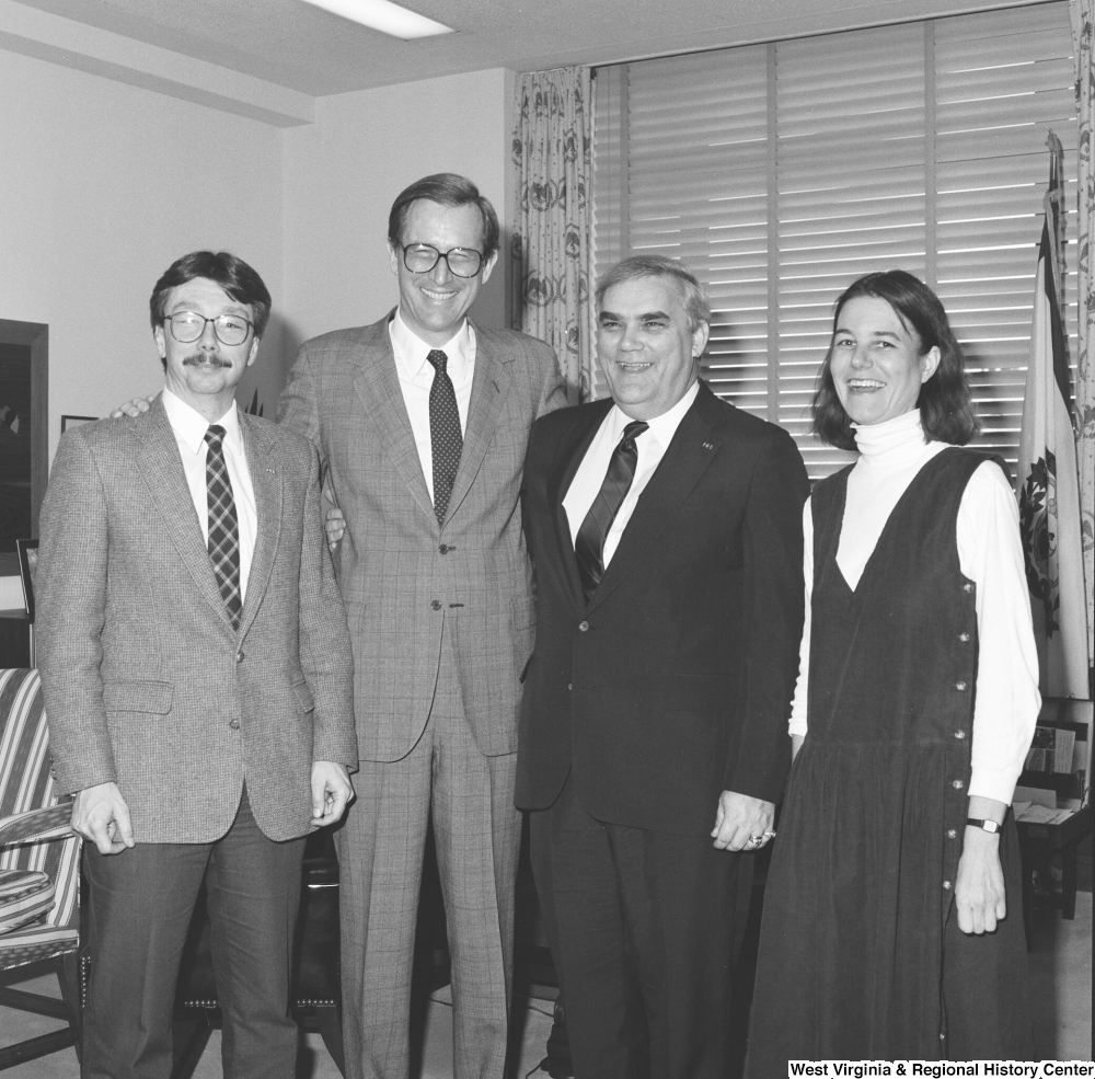 "[""Senator John D. (Jay) Rockefeller smiles for a photograph with three unidentified individuals in his office.""]%"