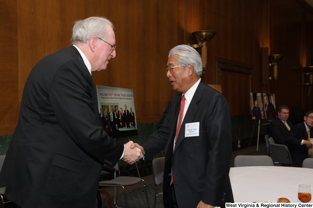 "[""Senator John D. (Jay) Rockefeller shakes hands with an industry leader during a Welcome to Washington luncheon.""]%"